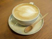 Una taza de café con el modelo del corazón en una taza blanca en la parte posterior de madera imagen de archivo