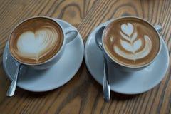Una taza de café con el modelo del corazón en una taza blanca en la parte posterior de madera Imagenes de archivo