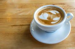 Una taza de café con el modelo del corazón en una taza blanca en tabl de madera Fotografía de archivo