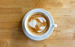 Una taza de café con el modelo del corazón en una taza blanca en tabl de madera Foto de archivo