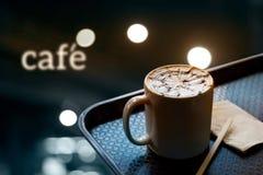 Una taza de café con el modelo del diseño en una taza blanca en la bandeja y y el café del texto en el fondo oscuro, foco suave Fotos de archivo libres de regalías