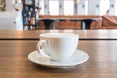 Una taza de café con espuma de la leche en la tabla de madera en café moderno fotografía de archivo