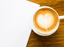 Una taza de café con forma del corazón y abre el libro en blanco imagen de archivo
