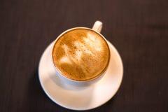 Una taza de café con una imagen en un café Fotografía de archivo libre de regalías