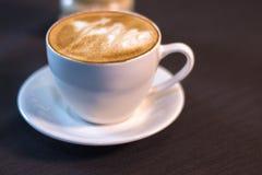 Una taza de café con una imagen en un café Foto de archivo libre de regalías