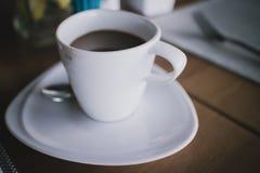 Una taza de café con la mancha del café en una taza con profundidad baja de Foto de archivo libre de regalías