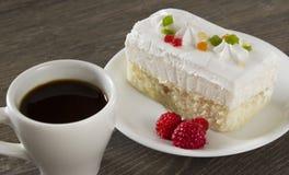 Una taza de café con la torta y las frambuesas Foto de archivo