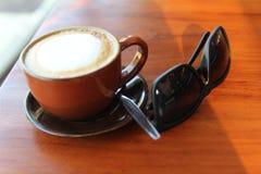 Una taza de café con las gafas de sol en la tabla Fotografía de archivo