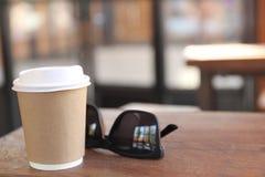 Una taza de café con las gafas de sol en la tabla Foto de archivo libre de regalías