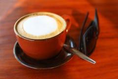 Una taza de café con las gafas de sol en la tabla Fotos de archivo libres de regalías