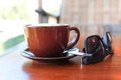 Una taza de café con las gafas de sol en la tabla Fotos de archivo