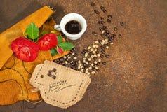 Una taza de café con las rosas rojas y los granos de café en textura oxidada Imagenes de archivo