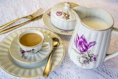 Una taza de café con leche y una tetera de leche Foto de archivo
