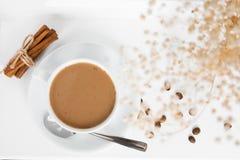 Una taza de café con los granos del canela y de café en una tabla blanca foto de archivo