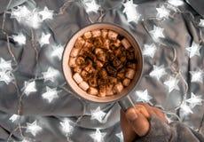 Una taza de café con los marsmallows y las luces de las estrellas imágenes de archivo libres de regalías