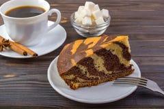 Una taza de café con los palillos de canela en una pequeña placa, una bifurcación, el pedazo de torta delicioso y un intestino co Fotos de archivo libres de regalías