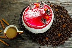 Una taza de café con una torta grande y los granos de café, el anís y el canela en una tabla de madera Imagen de archivo
