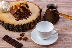 Una taza de café con un pedazo de torta en tocón de madera, una barra de chocolate, el anís, los granos de café y el cuenco con l Fotos de archivo