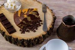 Una taza de café con un pedazo de torta en tocón de madera, una barra de chocolate, la bifurcación, los granos de café y el cuenc Imagenes de archivo