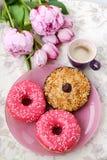 Una taza de café, de dulces y de flores color de rosa en la tabla Imagenes de archivo