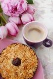 Una taza de café, de una galleta y de flores color de rosa en la tabla Foto de archivo