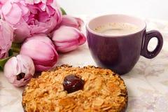 Una taza de café, de una galleta y de flores color de rosa en la tabla Imagenes de archivo