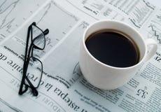 Una taza de café, de vidrios y de un periódico Imágenes de archivo libres de regalías
