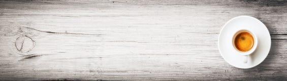 Una taza de café del café express en un tablón de madera imagenes de archivo