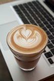 Una taza de café del latte en el teclado del ordenador portátil Foto de archivo libre de regalías