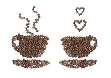 Una taza de café dobló de granos en un fondo blanco Imagen de archivo