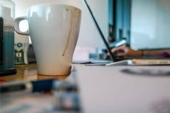 Una taza de café en el escritorio del trabajo con el trabajo inmóvil y el ordenador portátil en el fondo fotografía de archivo libre de regalías