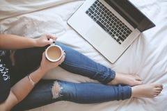 Una taza de café en la cama, ordenador portátil que espera por el lado fotografía de archivo