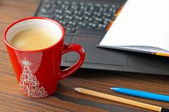 Una taza de café en la mesa, un ordenador portátil fotografía de archivo libre de regalías