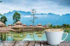 Una taza de café en la tabla de madera por el lago foto de archivo