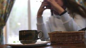 Una taza de café en una tabla en un café con una muchacha en el fondo con una falta de definición cámara lenta, 1920x1080, hd com almacen de metraje de vídeo