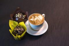 Una taza de café en un café con los postres Imagen de archivo libre de regalías