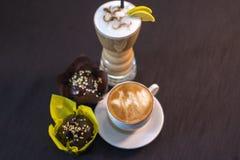 Una taza de café en un café con los postres Imágenes de archivo libres de regalías