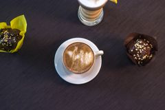Una taza de café en un café con los postres Foto de archivo libre de regalías