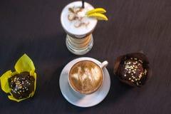 Una taza de café en un café con los postres Fotografía de archivo