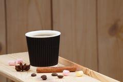 Una taza de café en un estante de madera, con canela, anís, los granos de café y la melcocha fotografía de archivo libre de regalías
