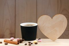 Una taza de café en un estante de madera, con canela, anís, los granos de café y la melcocha foto de archivo libre de regalías