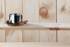 Una taza de café en un estante de madera, con los granos del canela, del anís y de café imagen de archivo