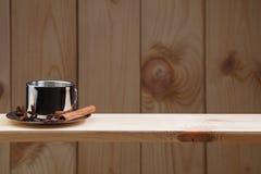 Una taza de café en un estante de madera, con los granos del canela, del anís y de café fotografía de archivo