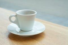 Una taza de café en un platillo en una tabla cerca de una ventana Fotos de archivo libres de regalías