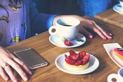 Una taza de café en un café y las manos de una muchacha Imagenes de archivo