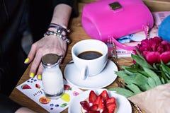 Una taza de café en un café y las manos de una muchacha Fotografía de archivo libre de regalías