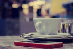Una taza de café en una bandeja y un teléfono elegante en una tabla imagen de archivo