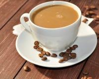 Una taza de café en una superficie de madera adornada con las habas del cofee Imágenes de archivo libres de regalías