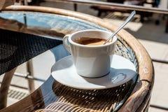 Una taza de café en una tabla de cristal Imágenes de archivo libres de regalías