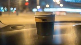 Una taza de café está en el tablero de instrumentos del coche fotografía de archivo libre de regalías